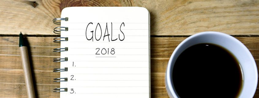 Text Goals 2018 on Notepad With Cup of Coffee